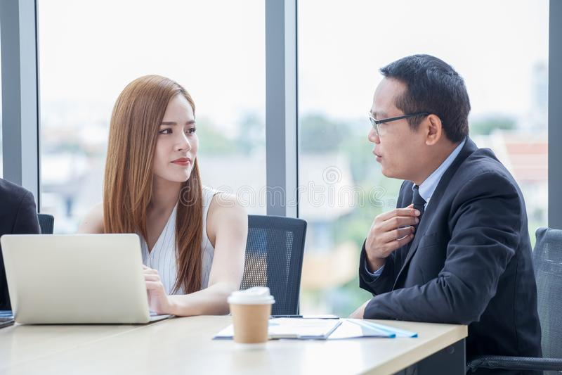 happy young businessman and businesswoman team working together with laptop computer on desk discussing information in office.boss stock photo