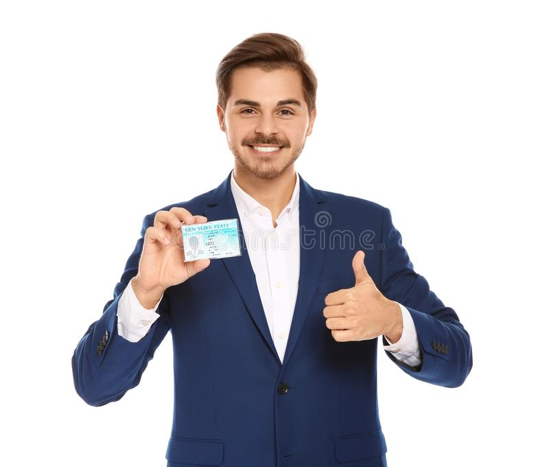 Happy young businessman with driving license. On white background stock image