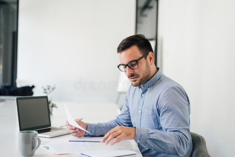 Happy young businessman looking at papers graphs and charts using laptop at his office desk stock image