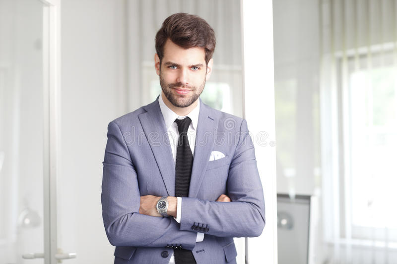 Happy young businessman. Portrait of smiling young businessman with arms crossed standing at office and looking at camera royalty free stock image