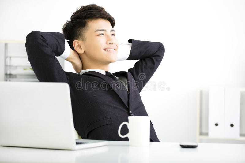 Happy young businessman relaxing in office royalty free stock photo