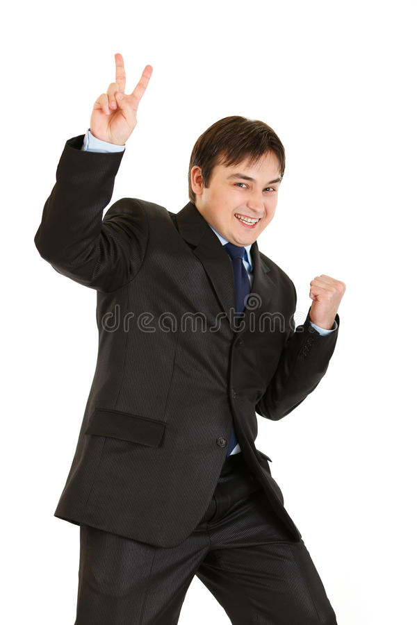 Happy young businessman showing victory gesture royalty free stock photos