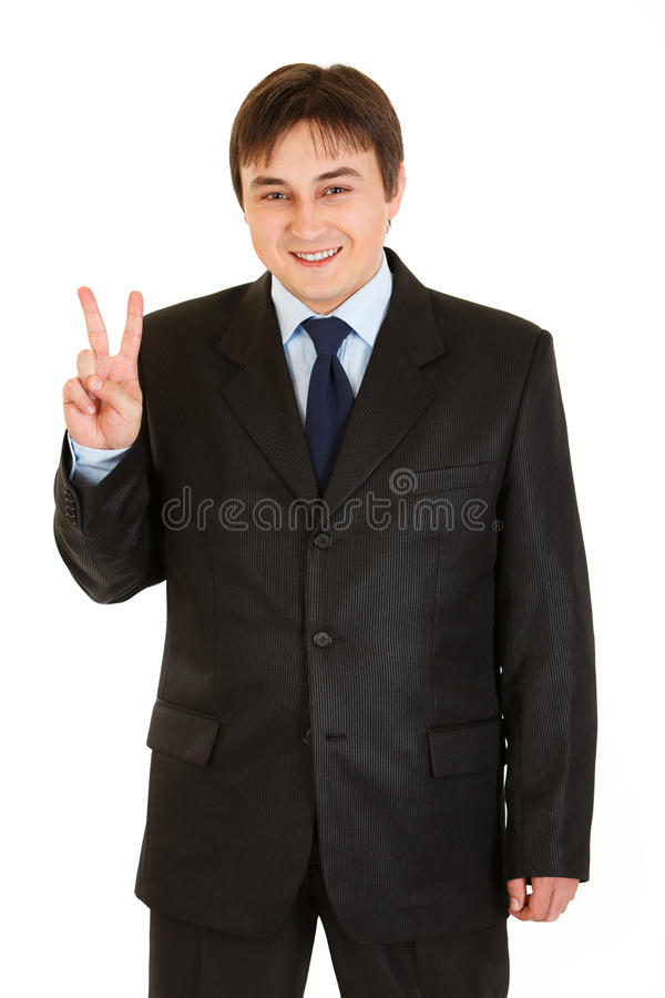 Happy young businessman showing victory gesture stock images