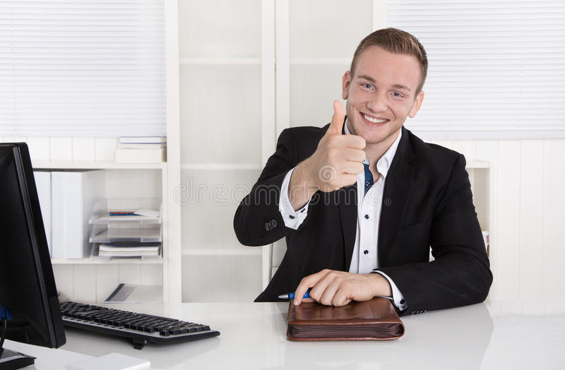 Happy young businessman sitting in his office making thumb up ge royalty free stock images