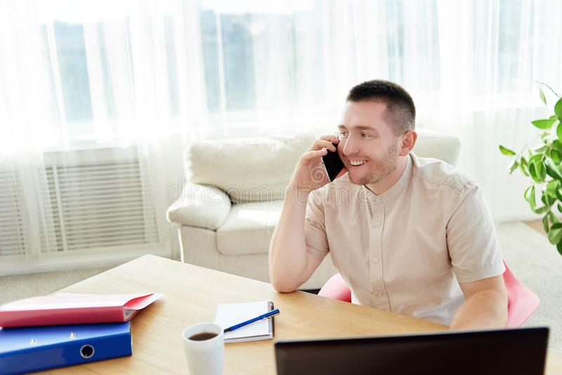 Happy young businessman sitting at wood desk, working on laptop and talking on mobile phone with client at home office, copy space royalty free stock images