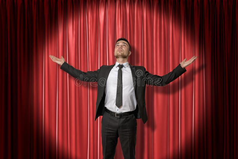 Happy young businessman standing and looking up with arms spread out to the side lit up by spotlight, against red stage royalty free stock photography
