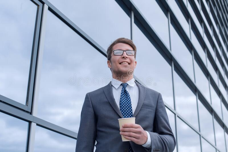 Happy young businessman standing near tall office building royalty free stock photos