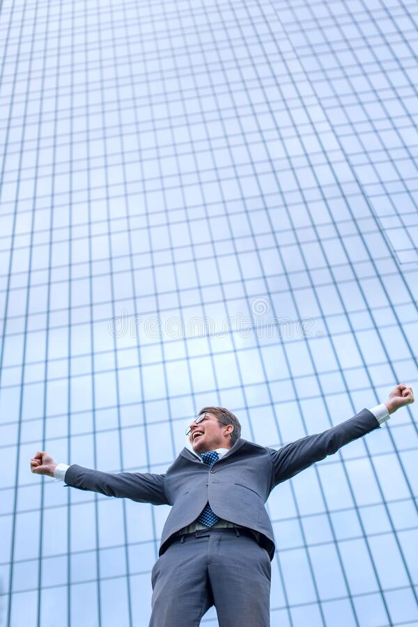 Happy young businessman standing on the street in front of the office stock photo