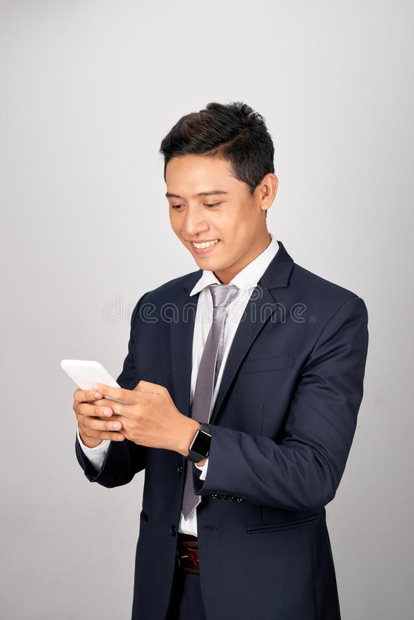 Happy young businessman texting to his colleague, friends, clients stock photography
