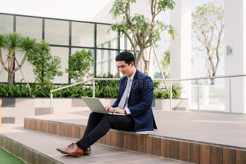 Happy young businessman using laptop outside office building stock image