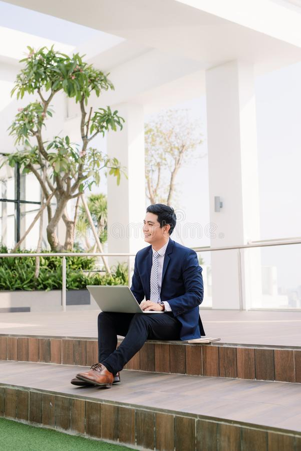 Happy young businessman using laptop outside office building.  stock photos