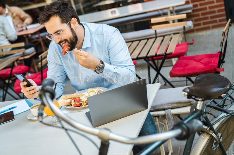 Businessman using phone while eating brunch. Happy young businessman using phone while eating brunch in a restaurant royalty free stock photos