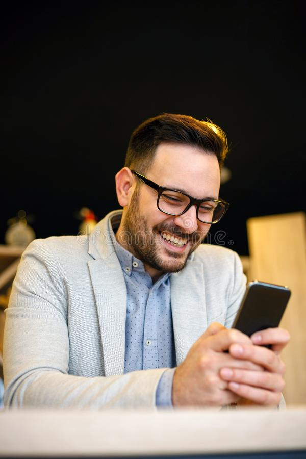 Happy young businessman using a smart phone in a cafe stock photo