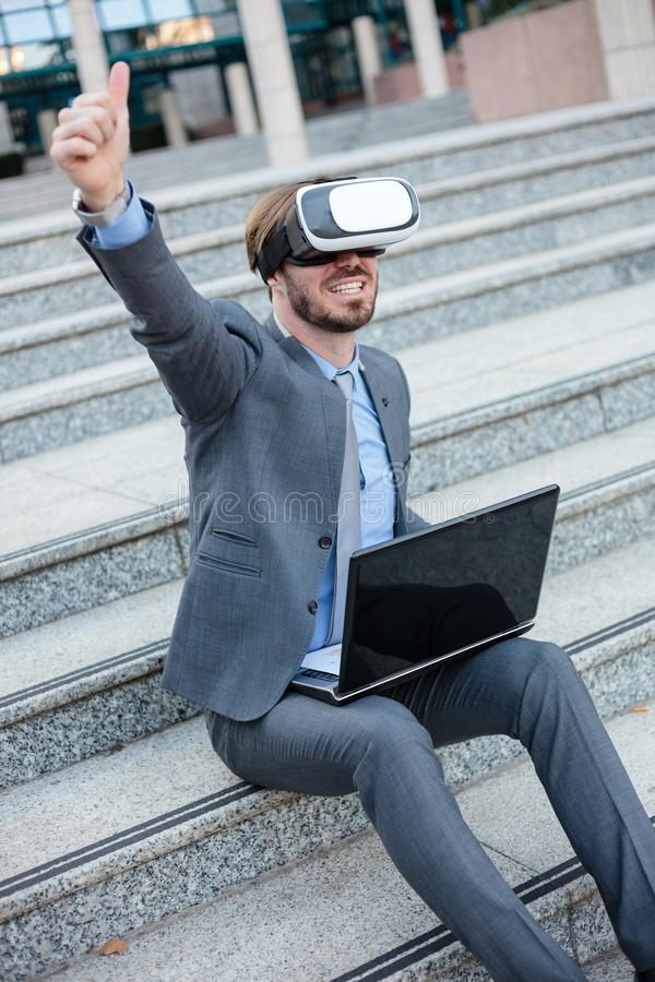 Happy young businessman using VR goggles, sitting in front of an office building with laptop. Celebrating success with arm high in royalty free stock photo