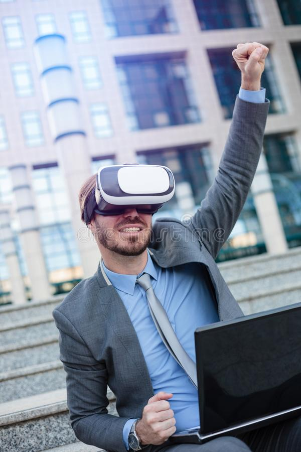 Happy young businessman using VR goggles, sitting in front of an office building. Celebrating success with fist high in the air royalty free stock images