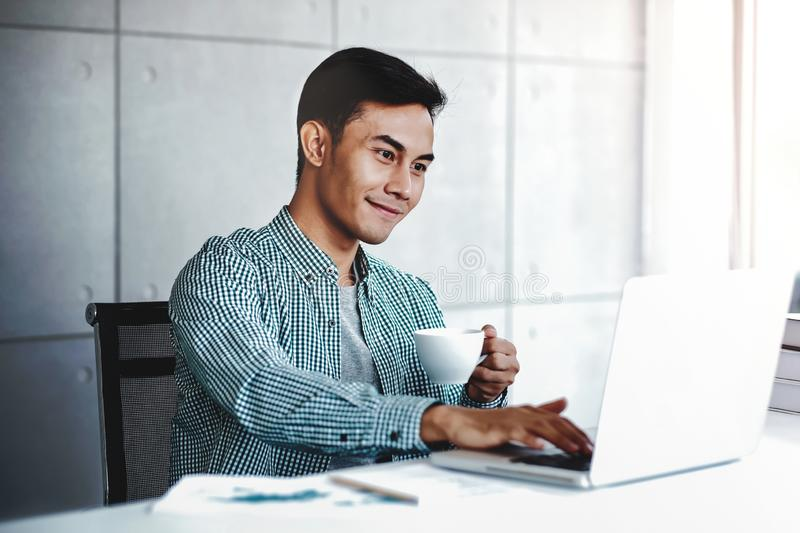 Happy Young Businessman Working on Computer Laptop in Office stock image