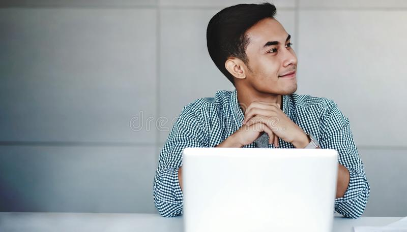 Happy Young Businessman Working on Computer Laptop in Office. Smiling stock photography