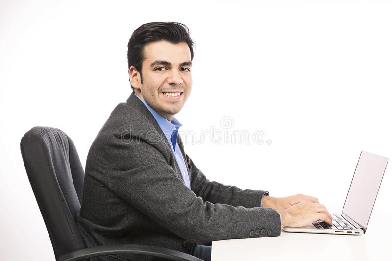 Happy young businessman working on laptop royalty free stock image