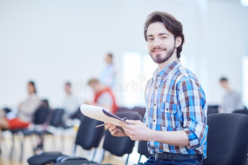 Guy in conference hall. Happy young businessman with working plan or report looking at camera in conference hall royalty free stock photography