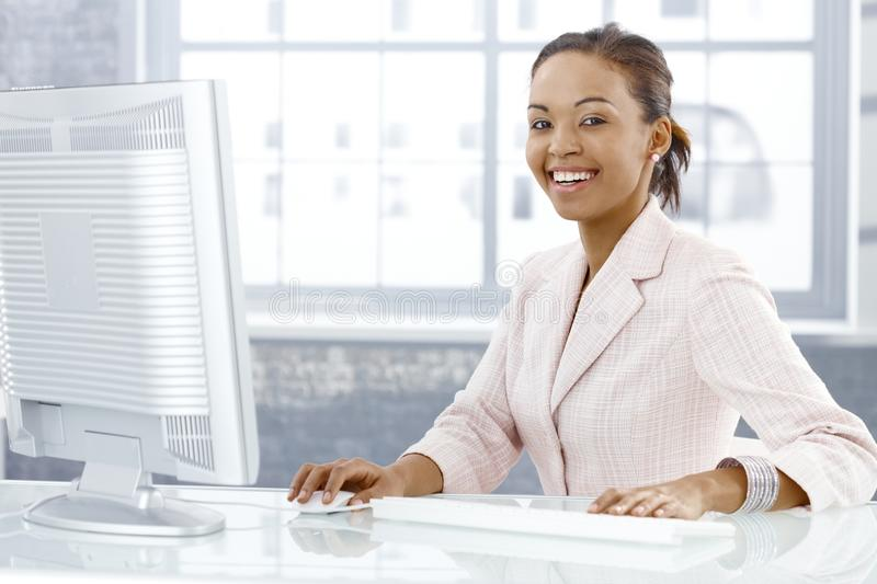 Happy young businesswoman. Sitting at desk, working on computer, laughing at camera royalty free stock photography