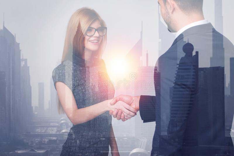 Happy young businesswoman and businessman handshake in city behind glass royalty free stock photography