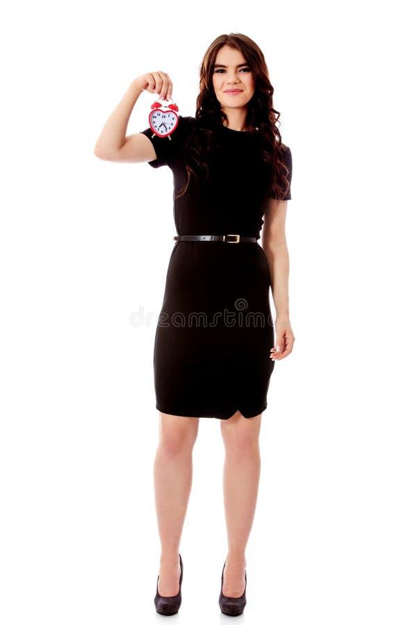 Happy young businesswoman holding alarm clock stock photo