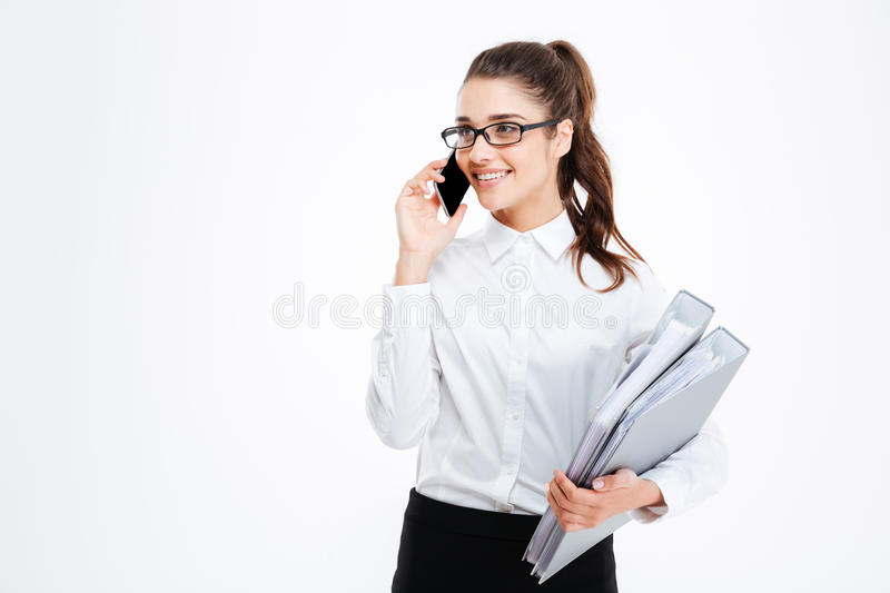 Happy young businesswoman holding folders and talking on mobile phone royalty free stock image