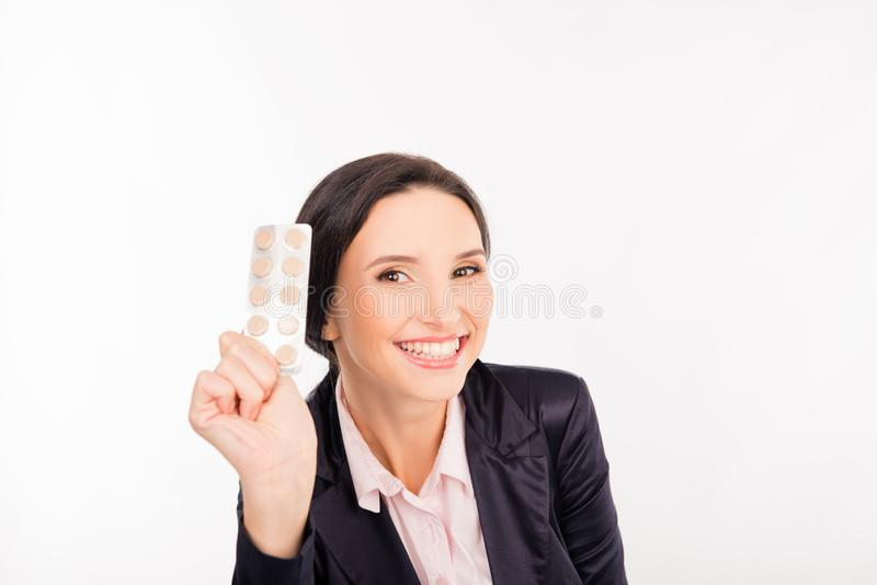 Happy young businesswoman holding a pill for a headache royalty free stock images