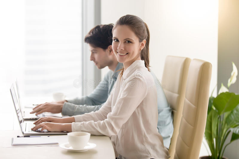 Happy young businesswoman looking at camera, working with male c stock photo