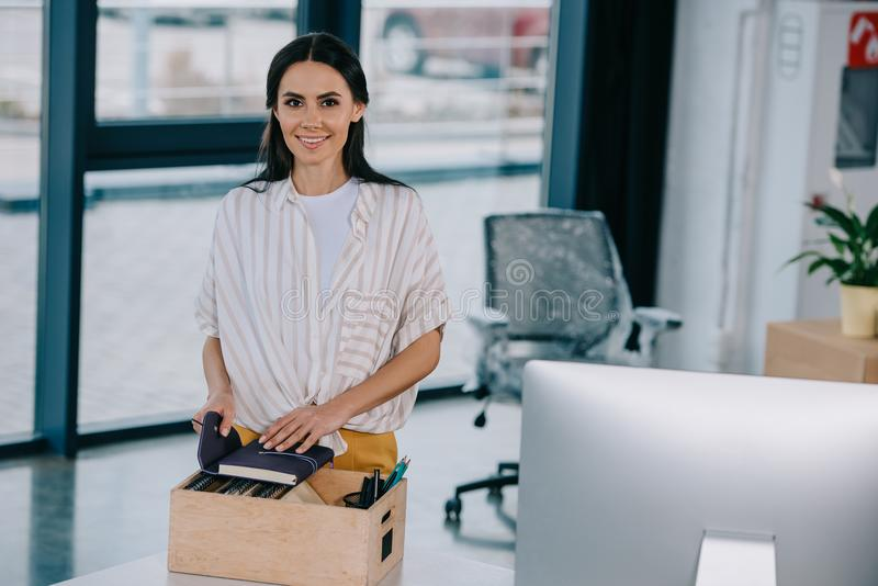 happy young businesswoman smiling at camera while unpacking office supplies royalty free stock photo