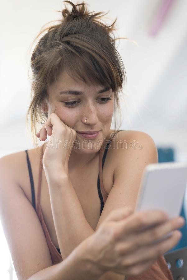Portrait of happy young businesswoman using mobile phone in offi royalty free stock images