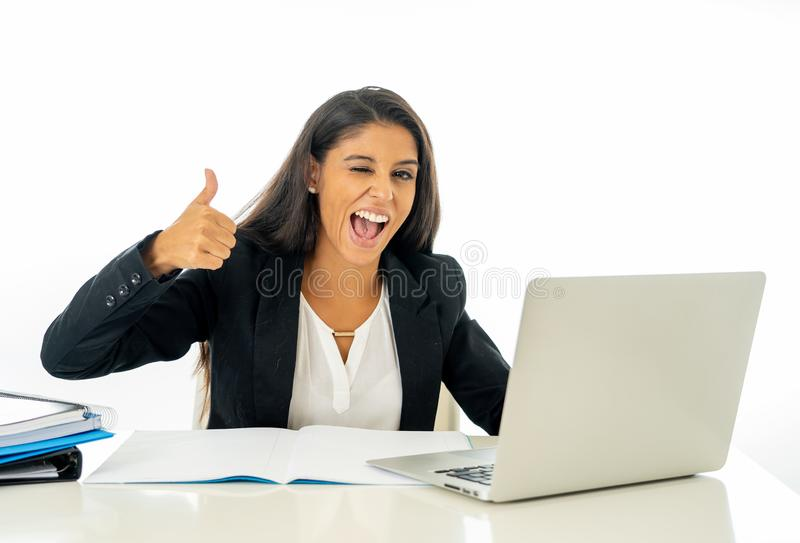 Happy young businesswoman working on her computer on her desk in satisfied at work and successful woman isolated on white royalty free stock image