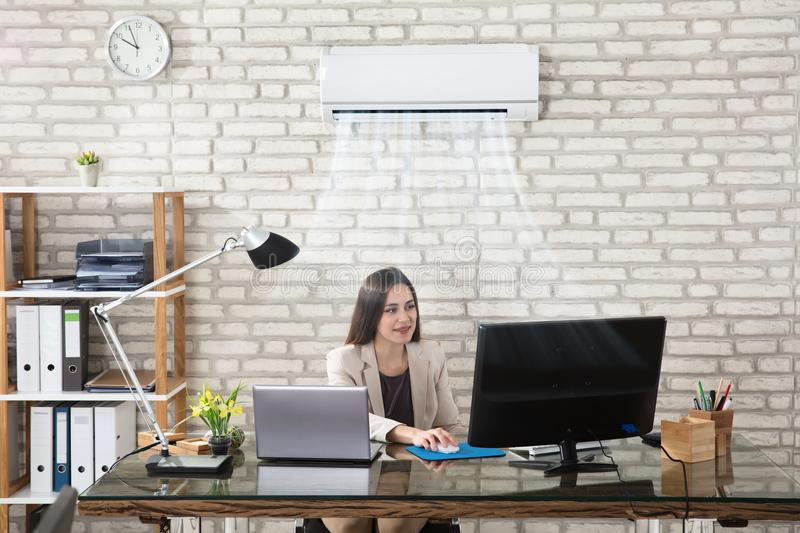 Businesswoman Working In Office With Air Conditioning stock image