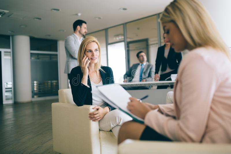 Happy young businesswomen doing paperwork in office royalty free stock photos