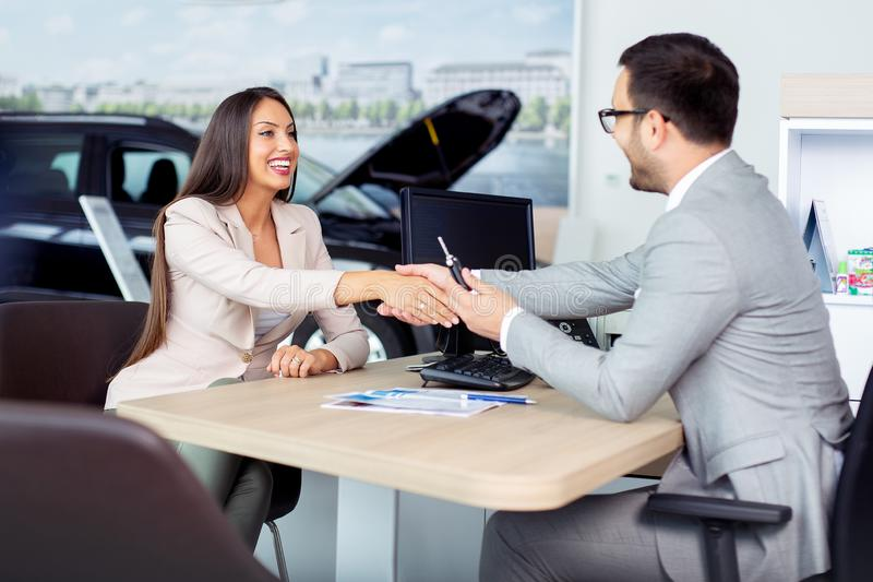 Happy car dealer and customer shake hands after successfully signed contract. Happy young car dealer and customer shake hands after successfully signed contract royalty free stock image