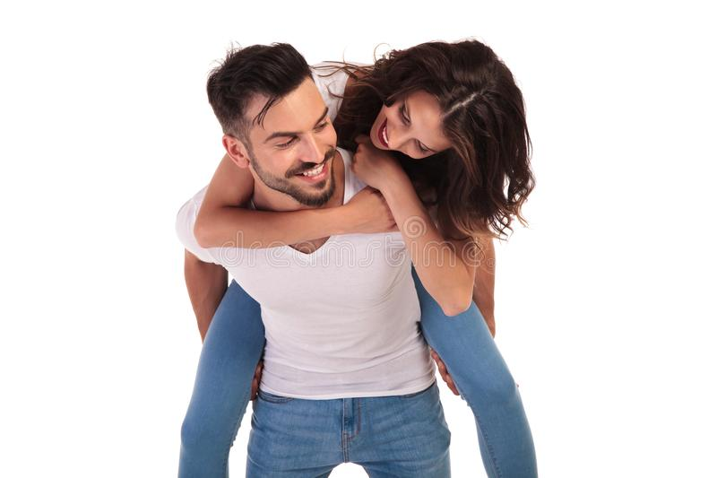 Happy young casual couple having fun together. On white background, men carrying his women on his back and laughs royalty free stock photo