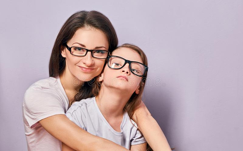 Happy young casual mother and smiling and hugging her kid in fashion glasses on purple background with empty copy space stock images