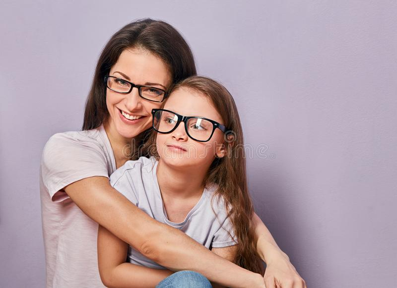 Happy young casual mother and smiling and hugging her kid in fashion glasses on purple background stock images