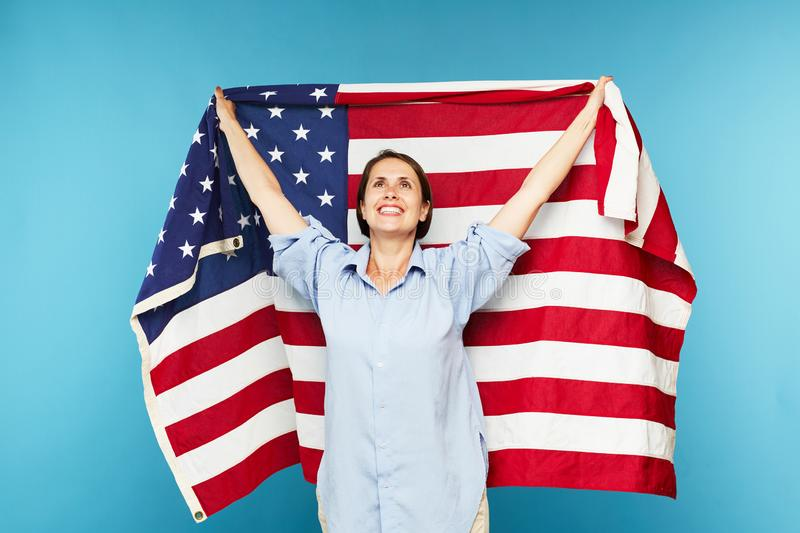 Happy young casual woman with large American flag royalty free stock photos