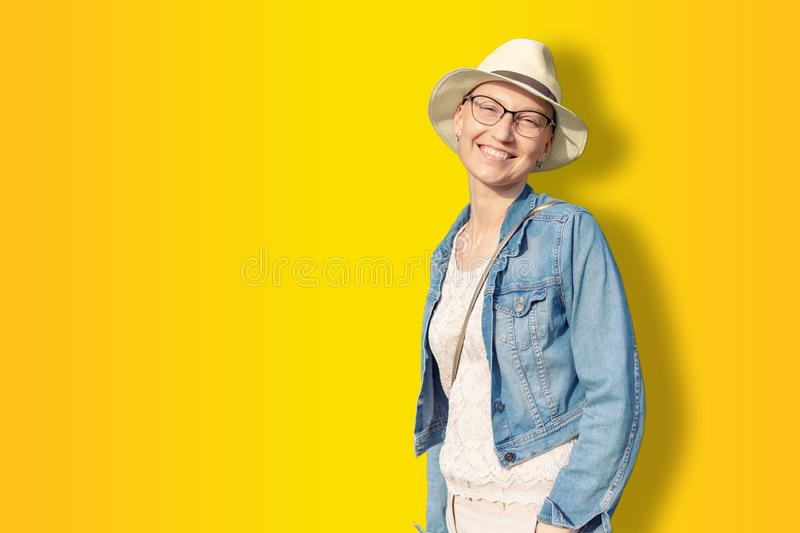 Happy young caucasian bald woman in hat and casual clothes enjoying life after surviving breast cancer. Portrait of beautiful. Hairless girl smiling  on golden royalty free stock photography