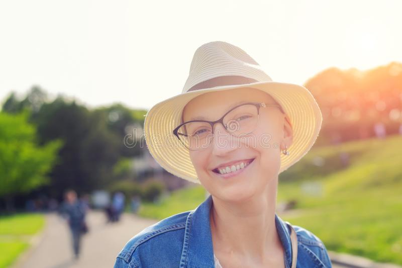 Happy young caucasian bald woman in hat and casual clothes enjoying life after surviving breast cancer. Portrait of beautiful royalty free stock photo