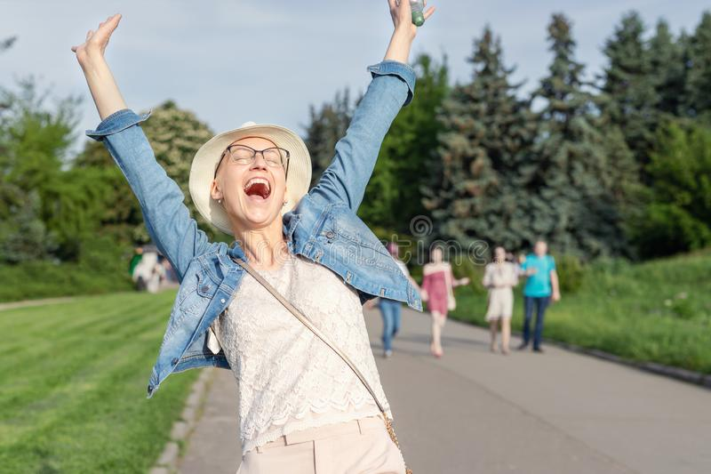 Happy young caucasian bald woman in hat and casual clothes enjoying life after surviving breast cancer. Portrait of beautiful stock photography