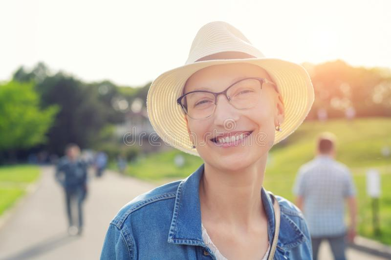 Happy young caucasian bald woman in hat and casual clothes enjoying life after surviving breast cancer. Portrait of beautiful royalty free stock photos