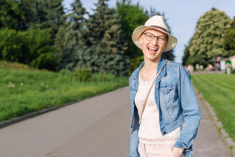 Happy young caucasian bald woman in hat and casual clothes enjoying life after surviving breast cancer. Portrait of stock photo