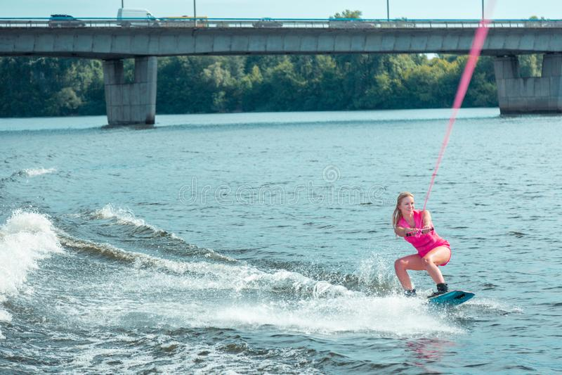 Happy young Caucasian blonde woman riding a wakeboard stock photo