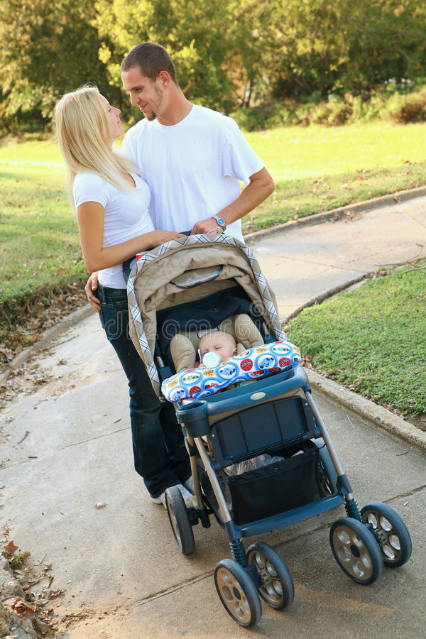 Happy Young Caucasian Couple Walking Their Baby stock photo