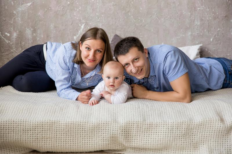 Happy Young Caucasian Family Lying on Bed stock images
