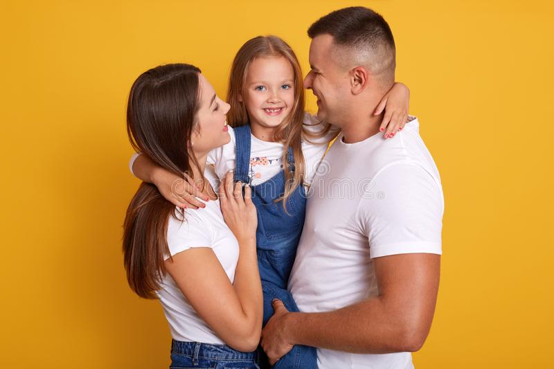 Happy young Caucasian family in photo studio. Father, mother and charming daughter. Parents hugging little adorable girl dressed royalty free stock image