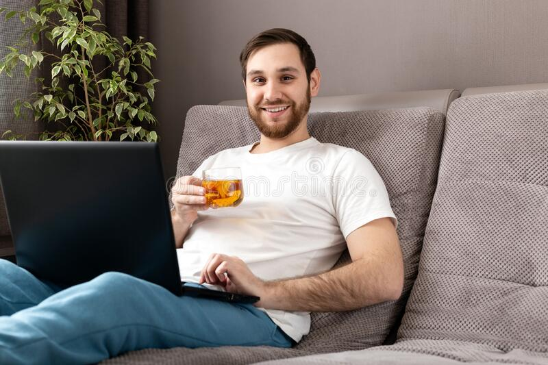 Happy young caucasian man drinks tea while working from home using laptop. Cozy Home office, workplace on sofa during coronavirus. Pandemic, covid 19 quarantine royalty free stock photo