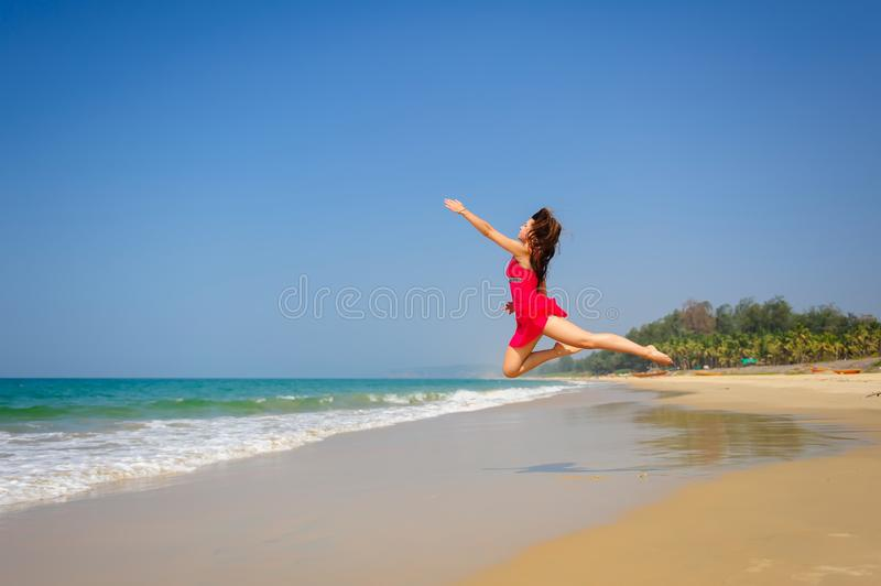 Happy young caucasian woman jumping high above wet sand in tropical sea on sunny day. Barefoot, a sporty girl in short red dress. Jumps and makes figures in the stock photography